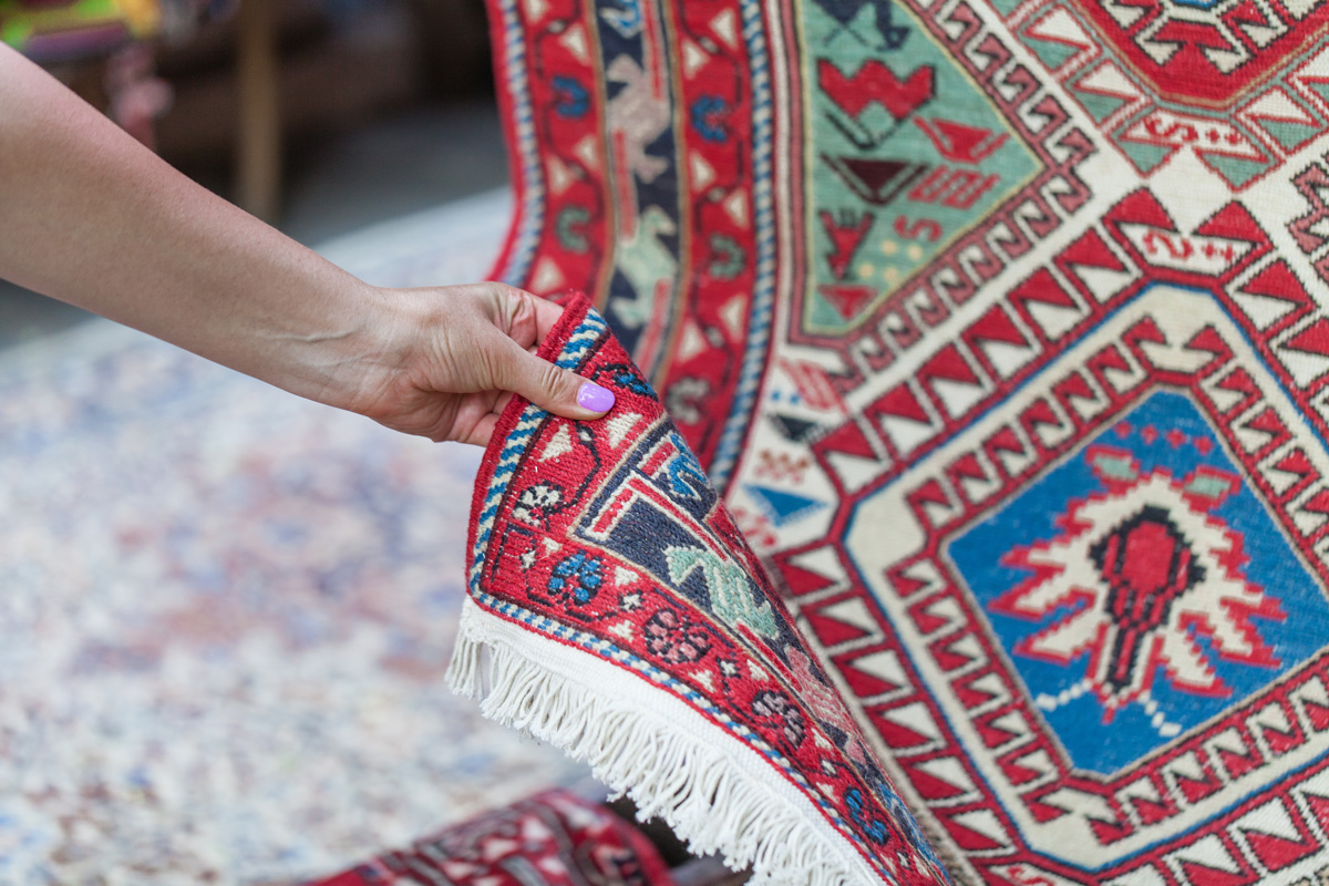 woman's hand touching oriental rug